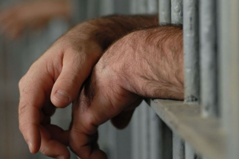 4555545 - mans hands behind bars in jail or prison