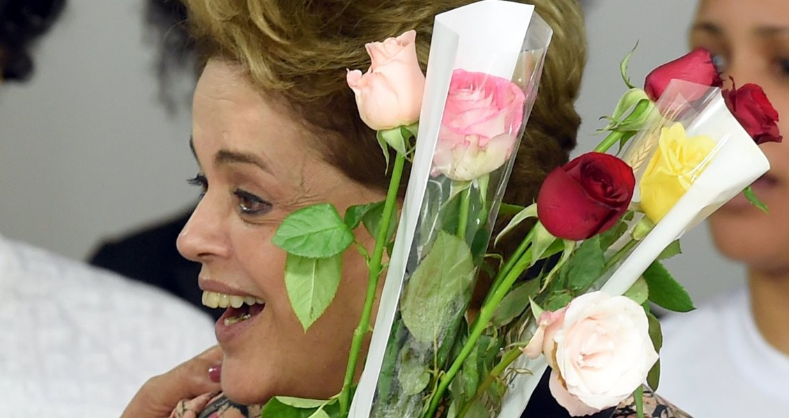 President Dilma Rousseff holds flowers during a meeting with women supporting their government and against her impeachment at Planalto Palace in Brasilia, on April 19, 2016. President Rousseff warned Tuesday that the impeachment process against her will deepen political instability in Brazil and said that sexism played a part in efforts to oust its first female head of state. / AFP PHOTO / EVARISTO SA