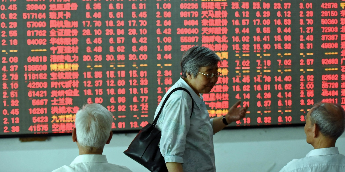 A Chinese investor (C) makes her way in front of a screen showing stock market movements at a securities firm in Hangzhou, eastern China's Zhejiang province on May 31, 2016.  Asian stocks rose on May 31, led by a surge in Shanghai, while the dollar edged higher as traders weighed the fallout from a likely US interest rate rise this summer. / AFP PHOTO / STR / China OUT