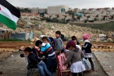 Palestinian bedouin children from the Abu Nawar community attend a class in the West Bank town of al-Azariya near the Jewish settlement of Maale Adumim (background), east of Jerusalem, on February 23, 2016. Israeli Army forces dismantled prefab classrooms and homes built with a donation from the French government, on February 20, and forced the children to attend their class outside without any infrastructure and under bad weather conditions. / AFP / AHMAD GHARABLI