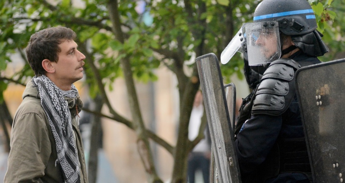 A protester faces police on May 12, 2016 in Nantes, western France, during a demonstration after the French government made use of the constitution's Article 49,3, allowing them to bypass parliament to force through a controversial labour reform bill. France's embattled Socialist government survived a vote of no-confidence on May 12 over its decision to force a controversial labour reform bill though parliament.  / AFP PHOTO / JEAN-FRANCOIS MONIER