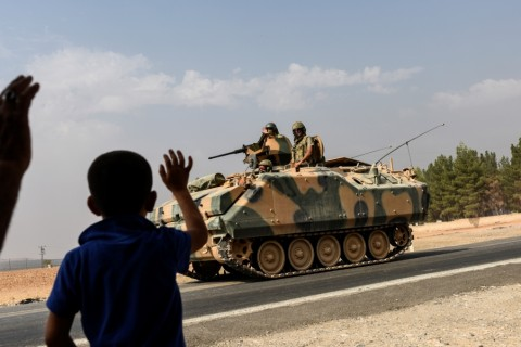 A Turkish boy waves to Turkish tank convoy driving into Syria from the Turkish Syrian border city of Karkamis in the southern region of Gaziantep, on August 26, 2016.  Turkey shelled Kurdish militia fighters in Syria on August 26 on the second day of a major military operation inside the country, saying they were failing to observe a deal with the US to stop advancing in jihadist-held territory. Turkey's army backed by international coalition air strikes launched an operation involving fighter jets and elite ground troops to drive Islamic State jihadists out of the border area. / AFP PHOTO / BULENT KILIC