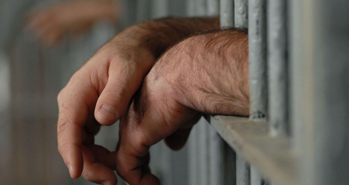 4555545 - mans hands behind bars in jail or prison