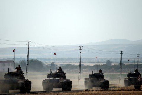 This picture taken around 5 kilometres west from the Turkish Syrian border city of Karkamis in the southern region of Gaziantep, on August 25, 2016 shows Turkish Army tanks driving to the Syrian Turkish border town of Jarabulus. Turkey's army backed by international coalition air strikes launched an operation involving fighter jets and elite ground troops to drive Islamic State jihadists out of a key Syrian border town. The air and ground operation, the most ambitious launched by Turkey in the Syria conflict, is aimed at clearing jihadists from the town of Jarabulus, which lies directly opposite the Turkish town of Karkamis. / AFP PHOTO / BULENT KILIC