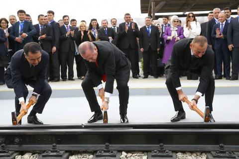 """""""Bakü-Tiflis-Kars Demiryolu"""" (BTK) hattının açılışı dolayısıyla, Cumhurbaşkanı Recep Tayyip Erdoğan (ortada), Azerbaycan Cumhurbaşkanı İlham Aliyev (sağda), Kazakistan Başbakanı Bakıtcan Sagintayev (solda) temsili çivi çakma törenine katıldı. Törene, Cumhurbaşkanı Erdoğan'ın eşi Emine Erdoğan (arka sağ 3) ve Azerbaycan Cumhurbaşkanı Aliyev'in eşi Mihriban Aliyeva (arka sağ 2) da katıldı."""