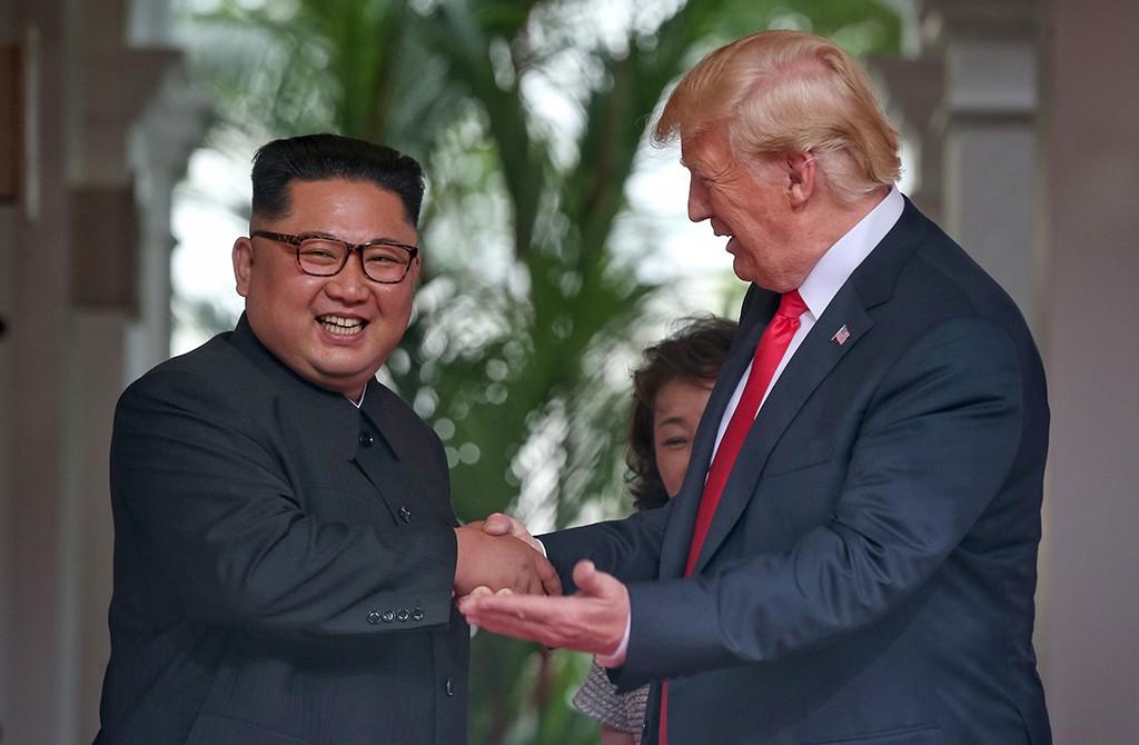 ABD Başkanı Donald Trump (sağda) ile Kuzey Kore lideri Kim Jong-un (solda), Singapur'un Sentosa Adası'ndaki Capella Otel'de tarihi zirvede ilk kez bir araya geldi. ABD ve Kuzey Kore bayraklarının önünde tokalaşarak objektiflere poz veren iki lider, daha sonra baş başa görüşmeyi yapacakları odaya beraber geçti. ( Singapur I·letişim ve Bilgi Bakanlığı - Anadolu Ajansı )