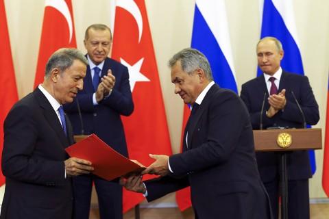 Soçi, Rusya   17 Eylül, 2018: Türkiye Milli Savunma Bakanı Hulusi Akar (solda) ve Rusya Savunma Bakanı Sergey Shoygu (sağdan ikinci); Türkiye Cumhurbaşkanı Recep Tayyip Erdoğan'ın Rusya Cumhurbaşkanı Vladimir Putin (arka sağda) ile ortak basın toplantısını takiben bir mutabakat zaptı imzaladıktan sonra belgeleri ellerinde bulunduruyorlar.