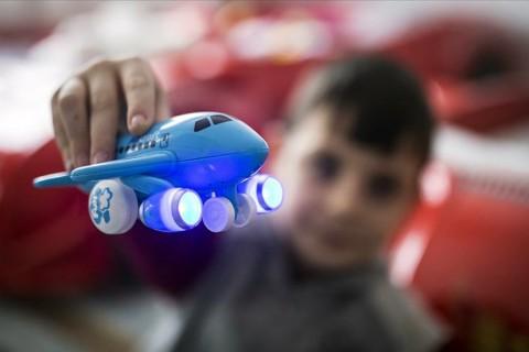 Uçak oyuncağıyla oynayan erkek çocuğu