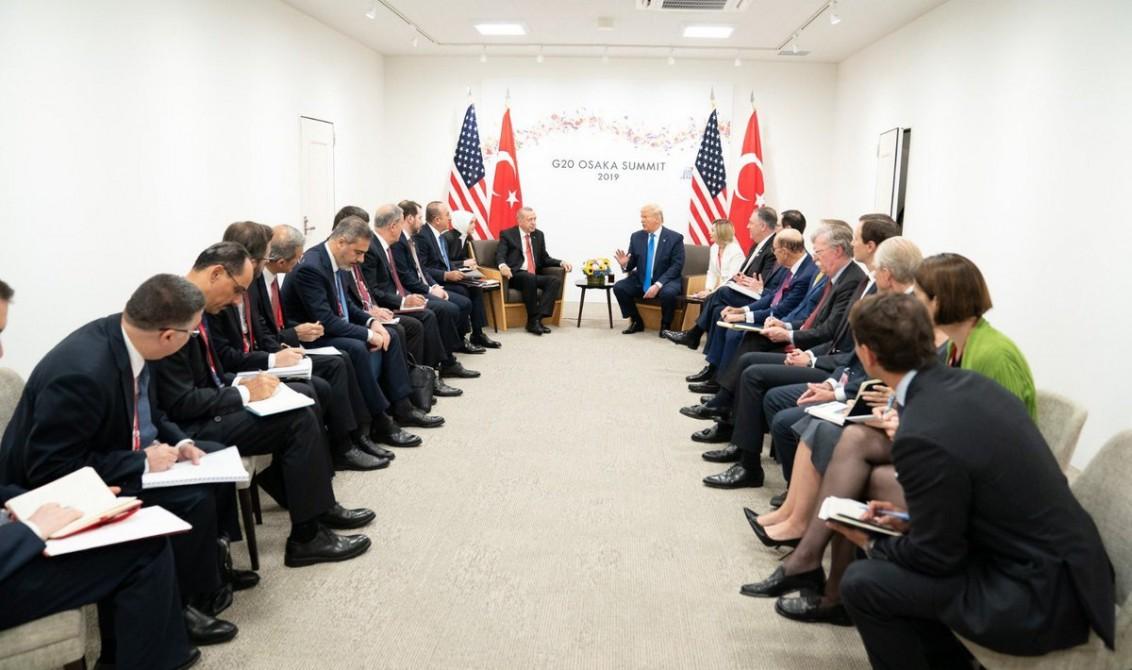 29 Haziran 2019   Türkiye Cumhurbaşkanı Recep Tayyip Erdoğan (orta solda), G20 Osaka Liderler Zirvesi kapsamında ABD Başkanı Donald Trump (orta sağda) ile bir araya geldi. Görüşmede, Dışişleri Bakanı Mevlüt Çavuşoğlu (sol 9), Milli Savunma Bakanı Hulusi Akar (sol 7), Hazine ve Maliye Bakanı Berat Albayrak (sol 8) ve MİT Başkanı Hakan Fidan (sol 5), AK Parti Genel Başkan Yardımcısı Cevdet Yılmaz (sol 4), Cumhurbaşkanlığı İletişim Başkanı Fahrettin Altun (sol 3), Cumhurbaşkanlığı Sözcüsü İbrahim Kalın (sol 2) ve Savunma Sanayi Müsteşarı İsmail Demir (solda) de yer aldı.