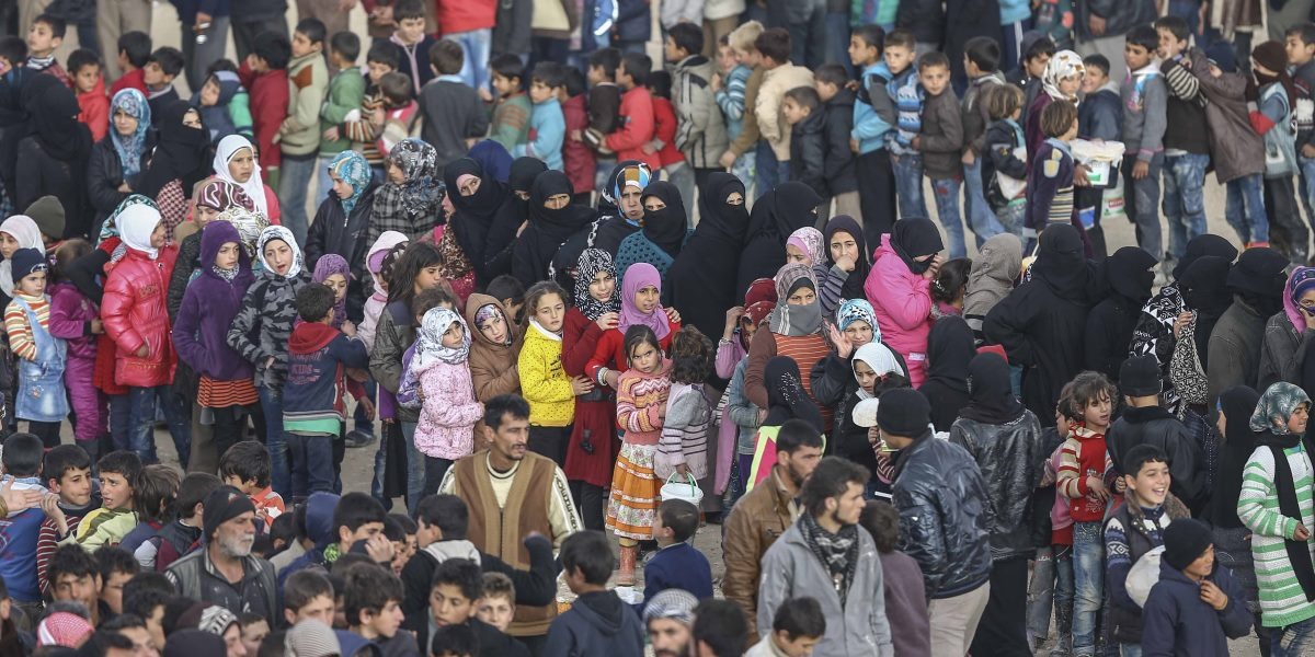 ALEPPO, SYRIA - FEBRUARY 10: Syrians, who fled bombing in Aleppo, wait in a queue to get food at a tent city and close to the Bab al-Salam border crossing on Turkish-Syrian border near Azaz town of Aleppo, Syria on February 10, 2016. Russian airstrikes have recently forced some 40,000 people to flee their homes in Syria's northern city of Aleppo. ( Fatih Aktaş - Anadolu Ajansı )