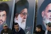 Lebanese sit in front of giant posters bearing portraits of Hassan Nasrallah, the head of Lebanon's militant Shiite Muslim movement Hezbollah (L), the founder of Iran's Islamic Republic, Ayatollah Ruhollah Khomeini (R) and Iran's supreme leader Ayatollah Ali Khamenei (C) on March 1, 2016, in the southern town of Kfour, in the Nabatiyeh district during the funeral of a Hezbollah fighter, Mohammed Hassan Nehme, who was killed while fighting alongside Syrian government forces in Syria. Mohammed Hassan Nehme was killed in the Syrian town of Khanasser, near Aleppo. The Syrian army retook the strategic town from the Islamic State group on February 26, 2016, paving the way for the reopening of its sole supply route to main northern city Aleppo.   / AFP / MAHMOUD ZAYYAT