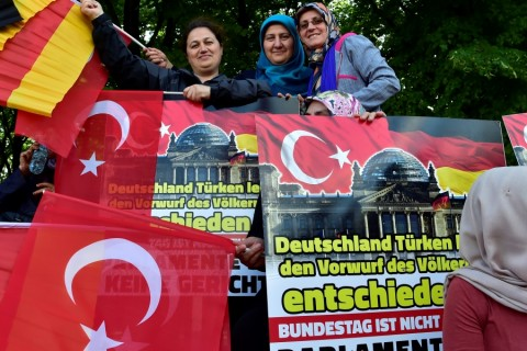 People with Turkish and German flags protest against the resolution German lawmakers are preparing to pass that recognises the massacre of Armenians by Ottoman forces as genocide, despite stark warnings from Turkey that the vote could hurt ties in front of the Brandenburg Gate in Berlin on June 1, 2016.  / AFP PHOTO / John MACDOUGALL