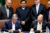 Farhad Parvaresh (L), Chairman and Managing Director of Iran Air, and Fletcher Barkdull (R), Boeing regional director, sign an agreement in the presence of Abbas Ahmad Akhoundi (C), Minister of Roads and Urban Development, in the capital Tehran on December 11, 2016. Iran Air finalised a contract to buy 80 planes from US firm Boeing, the official IRNA news agency, in the first deal of its kind since the 1979 Islamic revolution.  / AFP PHOTO / STR