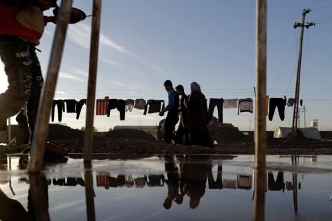 Iraqi refugees walk past the fence of the Khazir refugee camp near the Kurdish checkpoint of Aski Kalak, 40 km West of Arbil, the capital of the autonomous Kurdish region of northern Iraq, on November 21, 2016.  / AFP PHOTO / THOMAS COEX