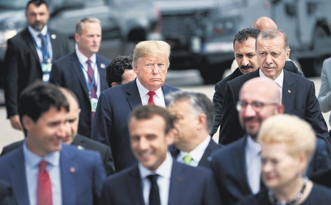 """U.S. President Donald Trump (L) and President Recep Tayyip Erdoğan (R) follow other leaders to a """"family photo """"during the summit at NATO headquarters, Brussels, July 11."""