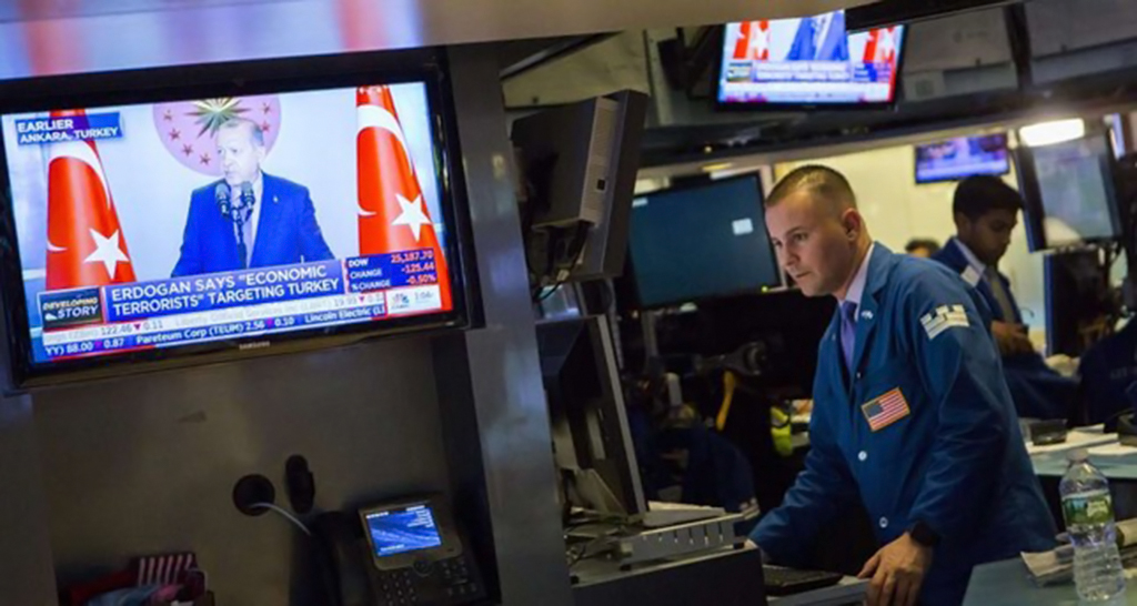 Traders on the floor of the New York Stock Exchange as President Erdoğan (shown on TV) speaks about the U.S. attacks against the Turkish economy, Aug. 13.