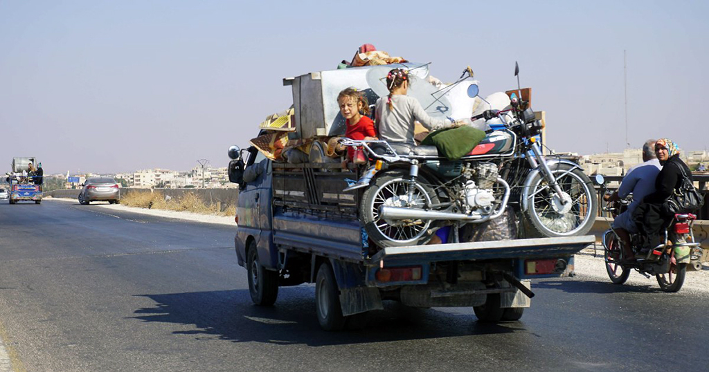 Syrian children on a truck loaded with furniture fleeing with their family from the conflict zone in Idlib; many others like them are preparing to leave the town due to the uncertain future of their homeland, Sept. 11.
