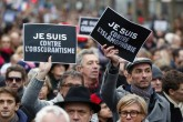 "Demonstrators hold posters reading ""I am against obscurantism"" (L) and ""I am against Islamophobia"" during a march in Paris following a bloody attack by Daesh members in the French capital that killed 17, Jan. 11, 2015."
