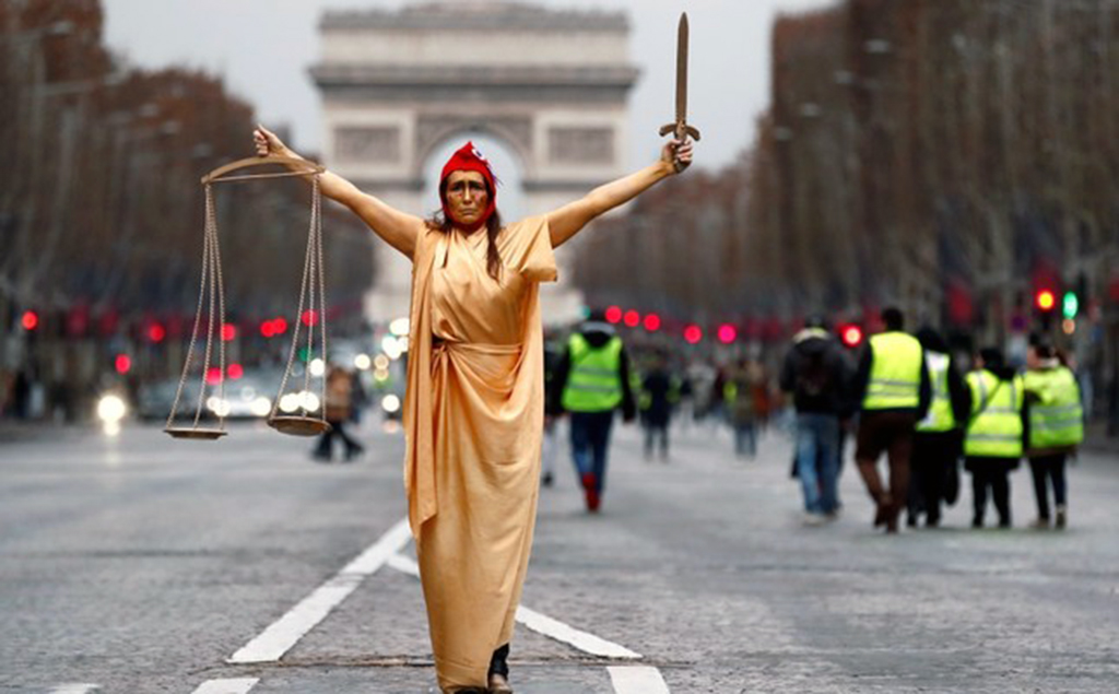 "A woman dressed as ""Marianne,"" a French symbol of justice, poses during a demonstration by the ""yellow vests"" movement at the Champs Elysees near the Arc de Triomphe, Paris, Dec. 22."