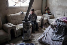 A Syrian boy sits inside a living room that was damaged by an airstrike in the opposition-held town of Orum al-Kubra, Aleppo, northern Syria, Jan. 5.