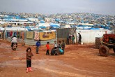 Children gather outside their makeshift shelters following torrential rain that affected a camp for displaced people near the town of Atme, close to the Turkish border, in Syria's mostly opposition-held northern Idlib province, Jan. 10.