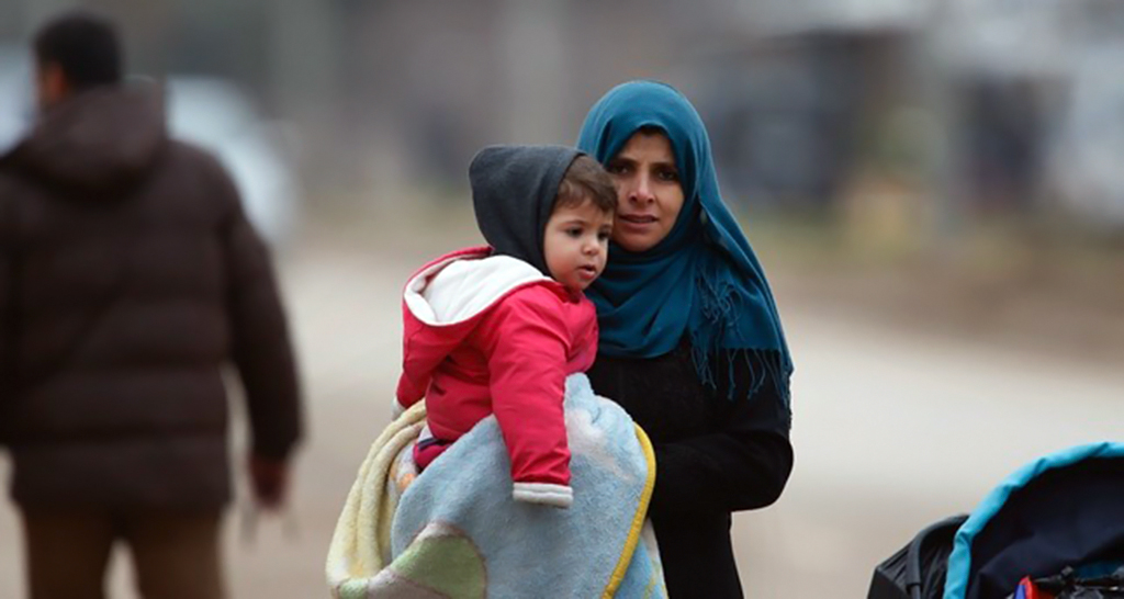 A Syrian woman holding a child walks towards Syria from Turkey at the Öncüpınar border crossing with Syria, Kilis, Turkey, Jan. 26. 2018.