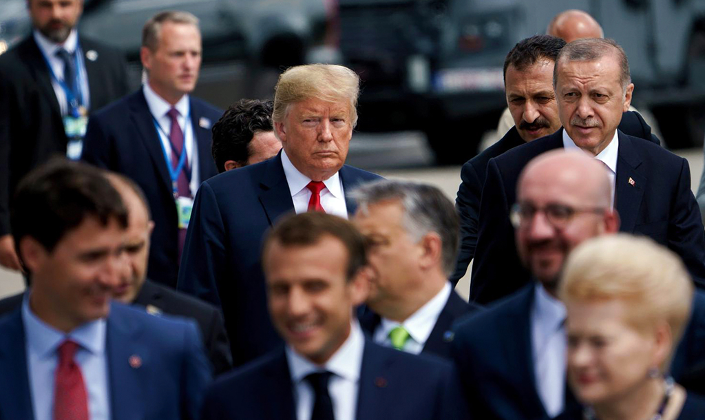 President Recep Tayyip Erdoğan (R) and U.S. President Donald Trump (L) talk during the walk to take the family photo at the NATO summit in Brussels, July 11, 2018.