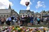 A group of students (C) sings in front of flowers left in tribute to victims at the Botanical Gardens in Christchurch on March 19, 2019, four days after a terrorist attack at two mosques that claimed the lives of 50 people.