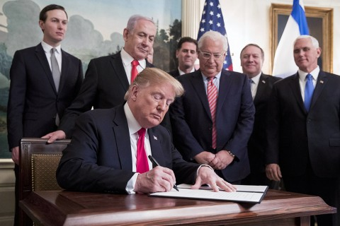 U.S. President Donald Trump (C) signs an order recognizing the Golan Heights as Israeli territory, in front of Prime Minister of Israel Benjamin Netanyahu (back C), in the Diplomatic Reception Room of the White House in Washington, March 25, 2019.
