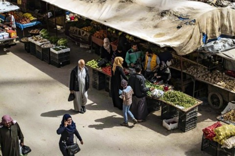 Customers walk near make-shift fruit and vegetable shops set in front of destroyed buildings in the northern Syrian city of Raqa, April 14, 2019.