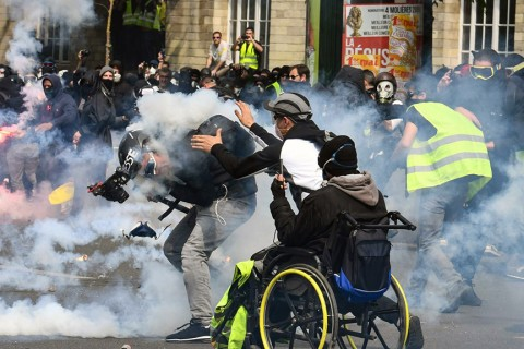"A cameraman reacts as he is hit by a tear gas canister as a ""yellow vest"" protester goes to help him during clashes with police in Paris, May 1, 2019."