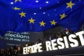 "A person sits on the steps waving the Belgian flag as a group of activists hold letters forming the words ""Europe Resists"" outside the European Parliament after the announcement of the results for European parliamentary elections, Brussels, May 26"