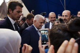 Binali Yıldırım (C), the Istanbul mayoral candidate from the ruling AK Party, surrounded by supporters and party officials as he visits a market before the June 23 rerun elections, Istanbul, June 11, 2019.
