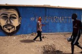Sudanese artist Asil Diab (L), walks in front of a mural painting of Mohamed Mattar, on the wall of a youth club in Bahri in Khartoum, July 21. Mattar was among dozens killed in the June 3 raid on a protest camp outside the military headquarters.