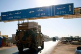 A Turkish military convoy drives along the Bab al-Hawa highway on their way to reinforce a Turkish military observation post in northwestern Syria, Aug. 24, 2019.