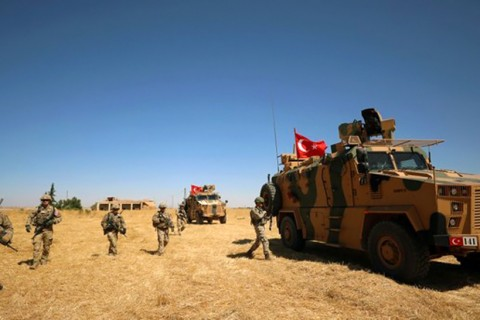 U.S. soldiers stand guard during a joint patrol with Turkish troops in the Syrian village of al-Hashisha, on the outskirts of Tal Abyad, along the border with Turkey, Sept. 8, 2019.