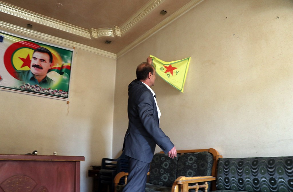 Construction engineer Muhammed Rummane removes the images of Abdullah Ocalan, leader of PKK, listed as a terrorist organization by Turkey, the U.S. and the EU, and other flags after finding out his house was turned into a headquarter by PKK and Syrian Kurdish YPG militia, which Turkey regards as a terror group, in northern Syria, in Ras al-Ayn, Syria on October 24, 2019.