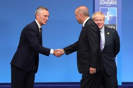 Turkish President Recep Tayyip Erdogan (C) and NATO Secretary General Jens Stoltenberg (L) shake hands during the NATO Leaders' Summit in London, United Kingdom on December 04, 2019.