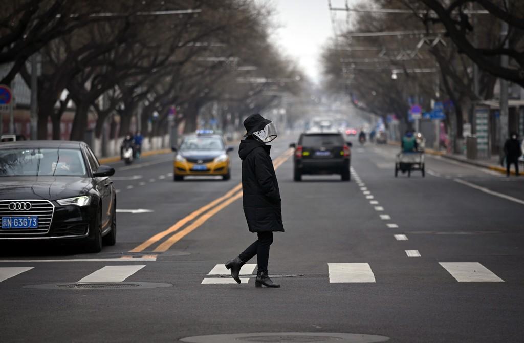 A woman wearing a face mask crosses a street in Beijing, Feb. 25, 2020. (AFP Photo)