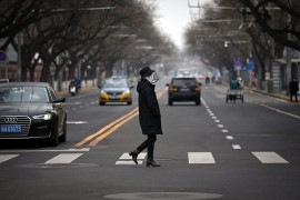 A woman wearing a face mask crosses a street in Beijing, Feb. 25, 2020. (AFP Photo)