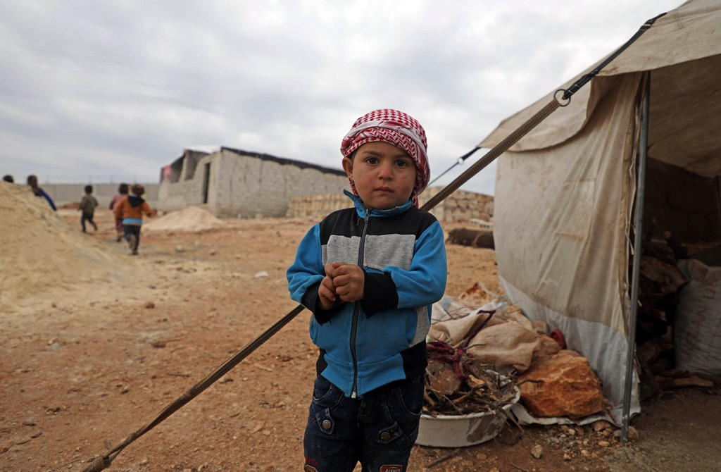 A displaced Syrian boy stands outside a tent at an informal camp in Kafr Lusin village on the border with Turkey in Syria's northwestern province of Idlib, Feb. 21, 2020. (AFP Photo)