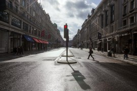 A few people stroll along a main shopping street at Regent Street, London, Saturday, March 14, 2020. (AP Photo)