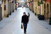 A man wearing a protective mask and gloves walks down a near empty St. Catherine Street in the southwestern French city of Bordeaux, Friday, March 20, 2020. (AFP Photo)