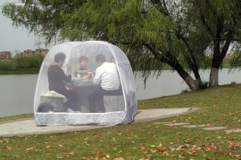 People enjoy a meal inside a tent to prevent the coronavirus disease, at a park in Nanjing, Jiangsu province, China, Tuesday, March 24, 2020. (Reuters Photo)