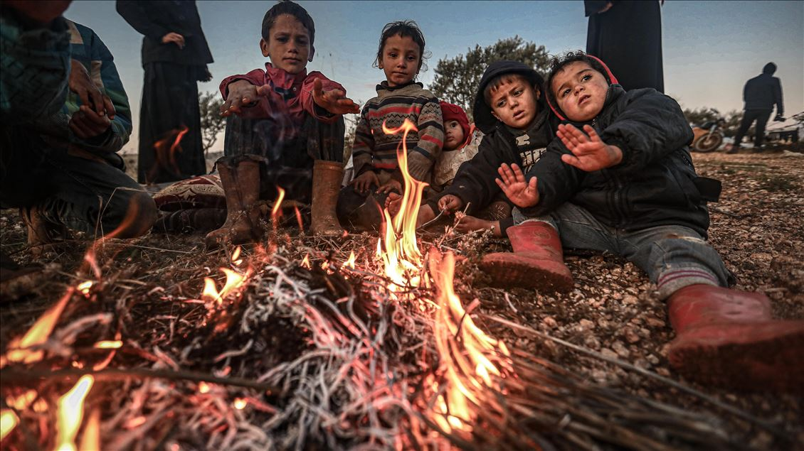 Syrian families, who have been forced to displace despite attacks carried out by Assad regime and Russia, sit on soil field despite the cold weather during winter season at Harbanush village in Idlib