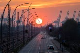 The sun sets behind an industrial cityscape in the port of Hamburg, Germany, April 11, 2020. (AP Photo)