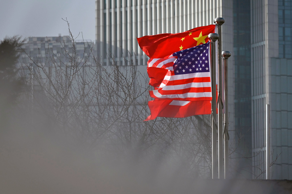 Chinese and U.S. national flags flutter at the entrance of a company office building in Beijing, China, Jan. 19, 2020. (AFP Photo)