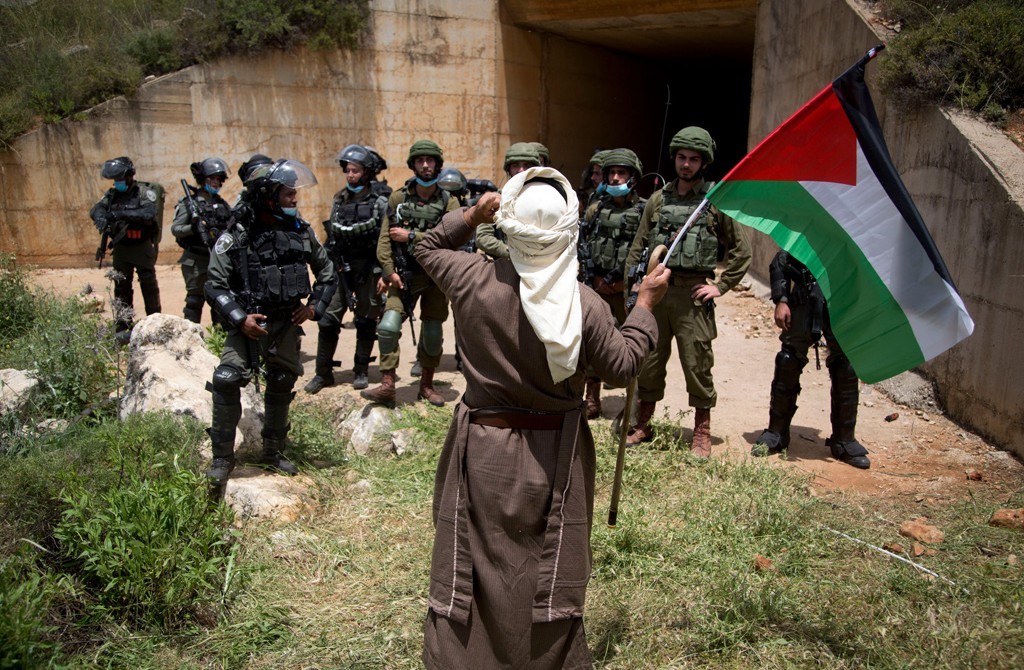 A Palestinian holds the national flag in front of Israeli border police during a protest marking the 72nd anniversary