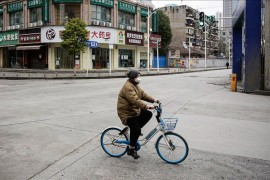 A woman wearing a protective face mask rides a shared bicycle on a street in Wuhan, the Chinese city where coronavirus originated, Hubei province, China.