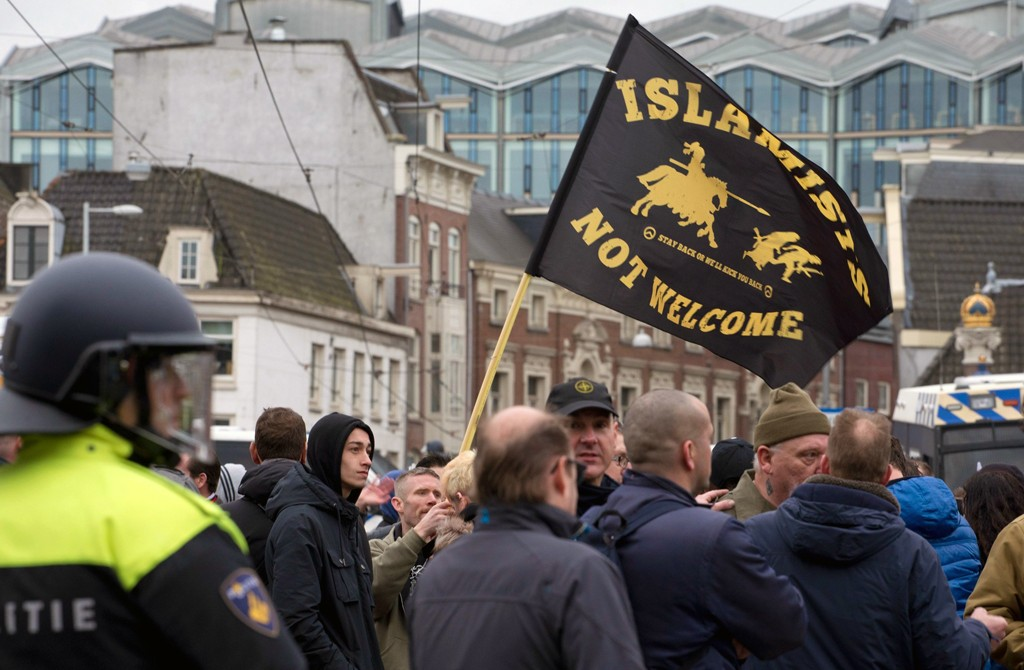 "Riot police separate pro- and anti- immigration demonstrators as a man waves a flag reading ""Islamists Not Welcome"" during a far-right Pegida demonstration in Amsterdam, Netherlands, Feb. 6, 2016. (AP Photo)"